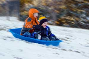photo of kids sliding down hill in snow